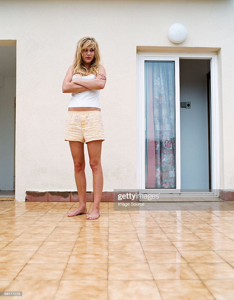 Serious woman standing outside apartment : Stock Photo