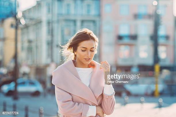 Serious woman walking outdoors on a cold sunny day