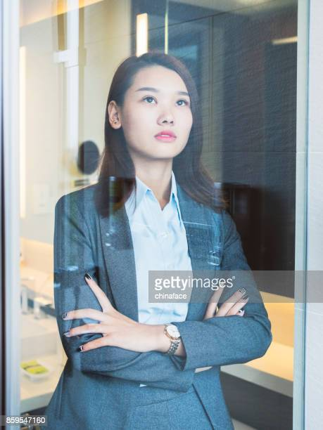 serious woman with arms crossed looking out of window