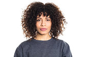 Portrait of serious young woman with short curly hair staring at camera on white background. Studio shot of female model wearing a t-shirt.