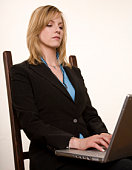 Serious young attractive businesswoman works on her laptop