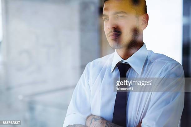 Serious young businessman behind glass pane