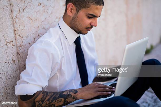 Serious young businessman sitting on the ground using his laptop