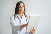 Serious young Caucasian woman in lab coat looking at tablet and touching screen. Portrait of pretty dark-haired female doctor studying medical report. Medical analysis concept