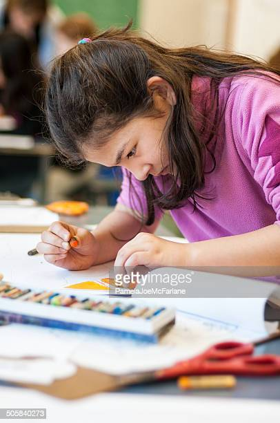 Serious Young Eurasian Girl Drawing in Art Class