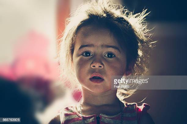 A serious young girl backlit by sunlight.