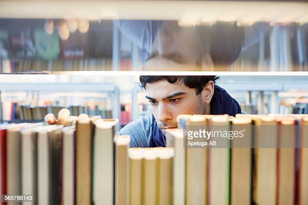 Serious young man choosing book in library