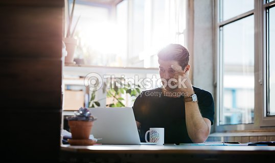 Serious young man finding ideas : Stock Photo