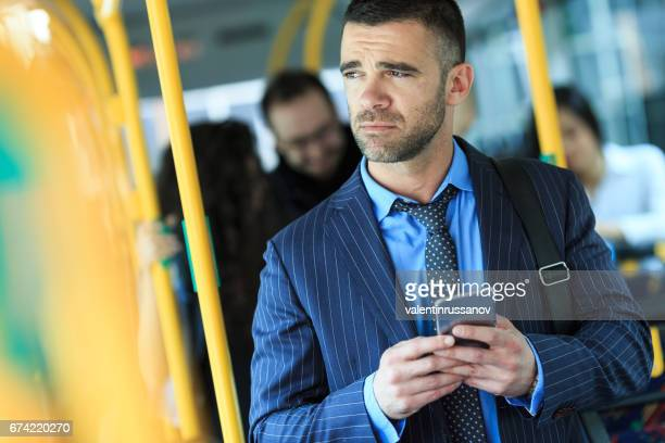Serious young man traveling and using smart phone