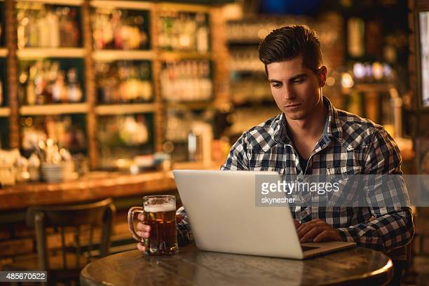 Serious young man using laptop in a bar.