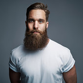 Single serious attractive young European man with muscular build and long fuzzy beard over gray background