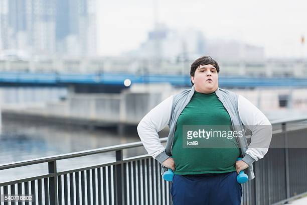 Serious young overweight man exercising outdoors