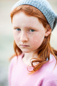 Serious young redheaded girl wearing stocking cap