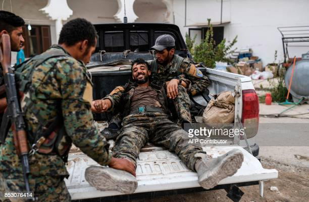 TOPSHOT A heavily wounded member of the Syrian Democratic Forces smiles as he arrives at a medical centre on the eastern frontline of Raqa on...