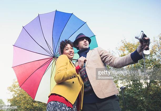 Serlfie fun - couple taking selfie with umbrella (London, UK)