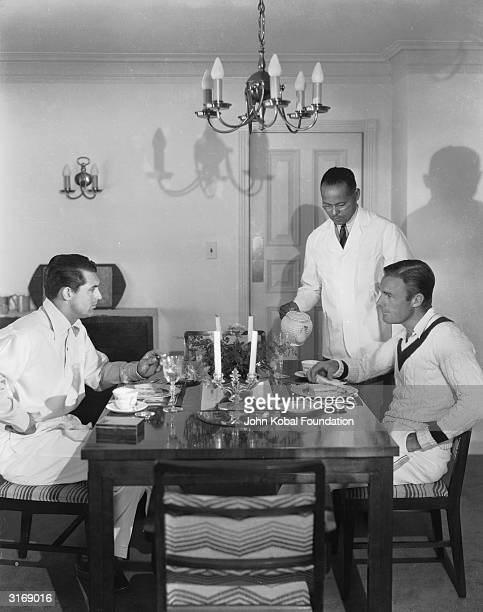 A servant pouring tea for the British born actor Cary Grant born Archibald Leach and the American actor Randolph Scott in the beach house which the...