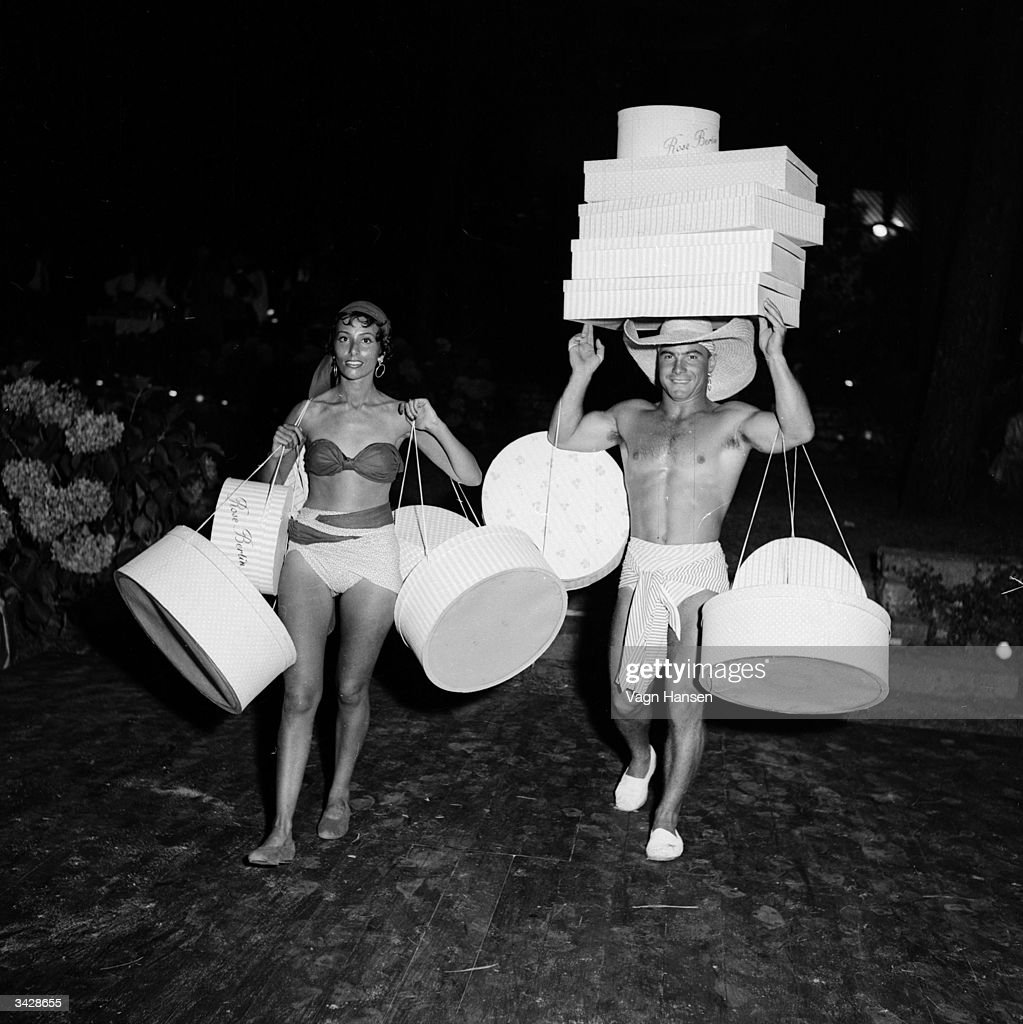 Servants in swimsuits carry hatboxes to and fro at a party organised by the Marquis de Cuevas as a publicity stunt for his Ballet company