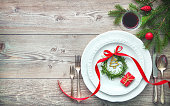 Served dinner table elegant arranged with Christmas decorations, rosemary wreath and gift box