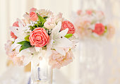 Served table for event dinner, decorated with floral compositions in vases in pink and coral shades. Wedding bouquet.