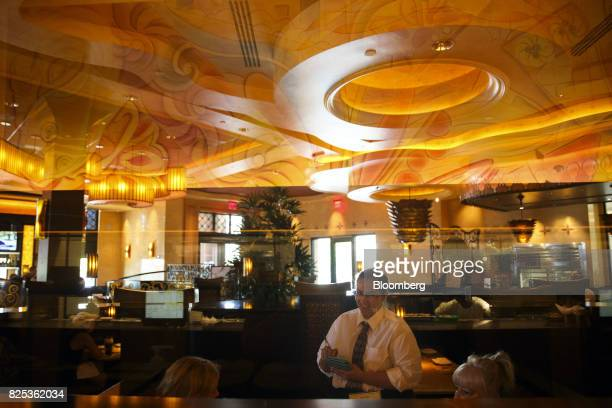 A server attends to customers as they dine at a Cheesecake Factory Inc restaurant in the Canoga Park neighborhood of Los Angeles California US on...