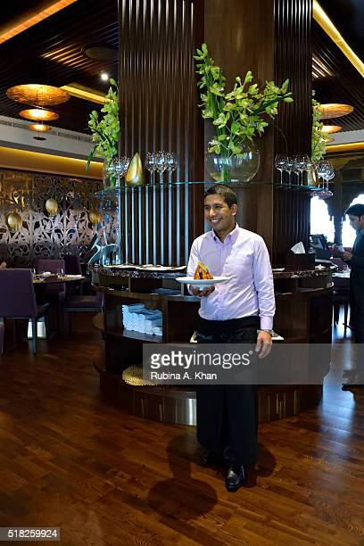 A server brings out Dum Ke Champen at Michelinstarred chef Vikas Khanna's restaurant Junoon at the ShangriLa hotel on March 30 2016 in Dubai United...