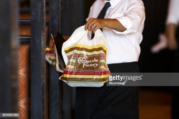 A server carries a togo bag of food to diners at a Cheesecake Factory Inc restaurant in the Canoga Park neighborhood of Los Angeles California US on...