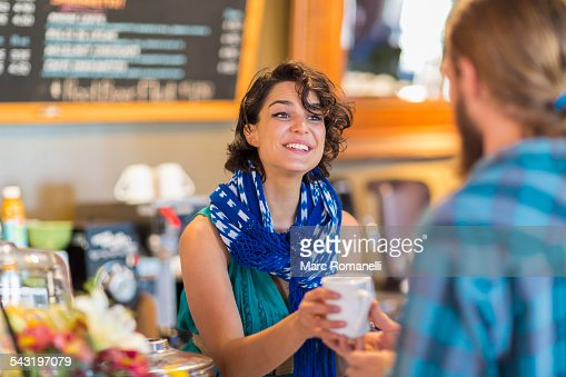 Server giving cup of coffee to customer in cafe : Stock Photo