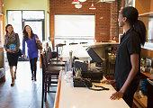 Server greeting customers in restaurant