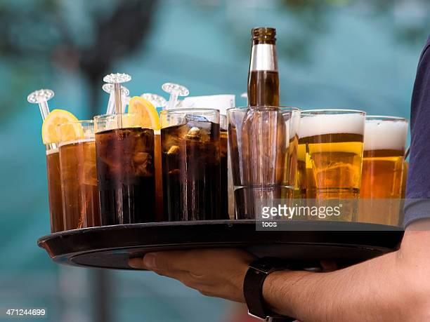 Server holding a tray of various types of drinks