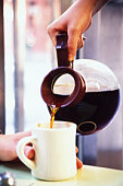 Server pouring coffee into coffee cup