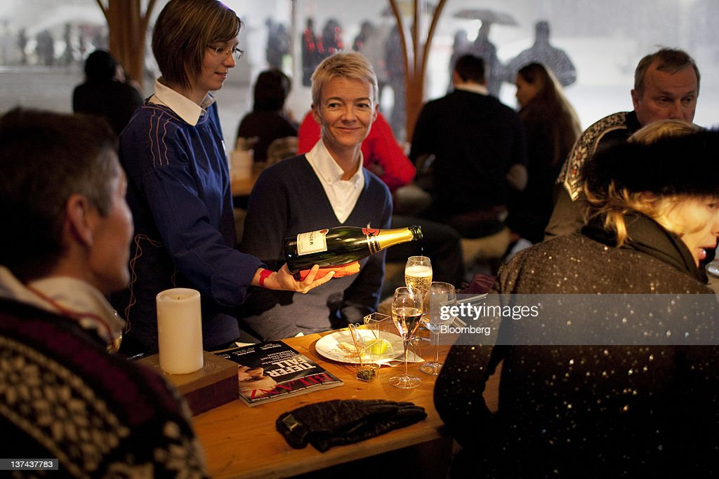 A server pours champagne for patrons in the VIP tent at the annual Klosters Snow Polo event in Klosters, Switzerland, on Friday, Jan. 20, 2012. German Chancellor Angela Merkel will open next week's World Economic Forum in Davos, Switzerland, which will be attended by policy makers and business leaders including U.S. Treasury Secretary Timothy F. Geithner. Photographer: Scott Eells/Bloomberg via Getty Images