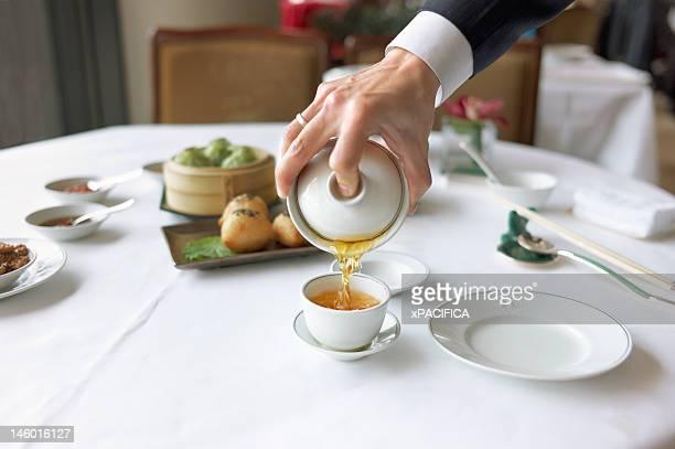 A server pours tea.