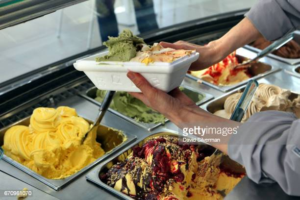 A server prepares a takeaway selection of freshlymade Italian gelato icecream at the Carpigiani company's onsite gelateria on March 28 2017 in...