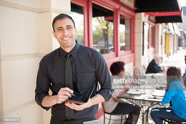 Server with notebook at sidewalk cafe