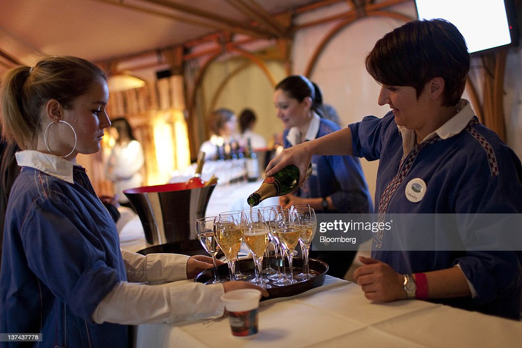 Servers pour champagne in the VIP tent at the annual Klosters Snow Polo event in Klosters, Switzerland, on Friday, Jan. 20, 2012. German Chancellor Angela Merkel will open next week's World Economic Forum in Davos, Switzerland, which will be attended by policy makers and business leaders including U.S. Treasury Secretary Timothy F. Geithner. Photographer: Scott Eells/Bloomberg via Getty Images