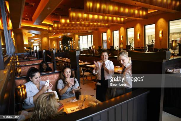 Servers sing happy birthday to a diner at a Cheesecake Factory Inc restaurant in the Canoga Park neighborhood of Los Angeles California US on Tuesday...