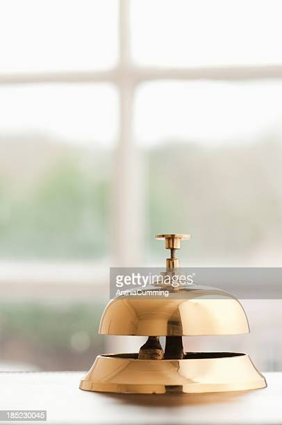 Service bell on desk beside window with copy space