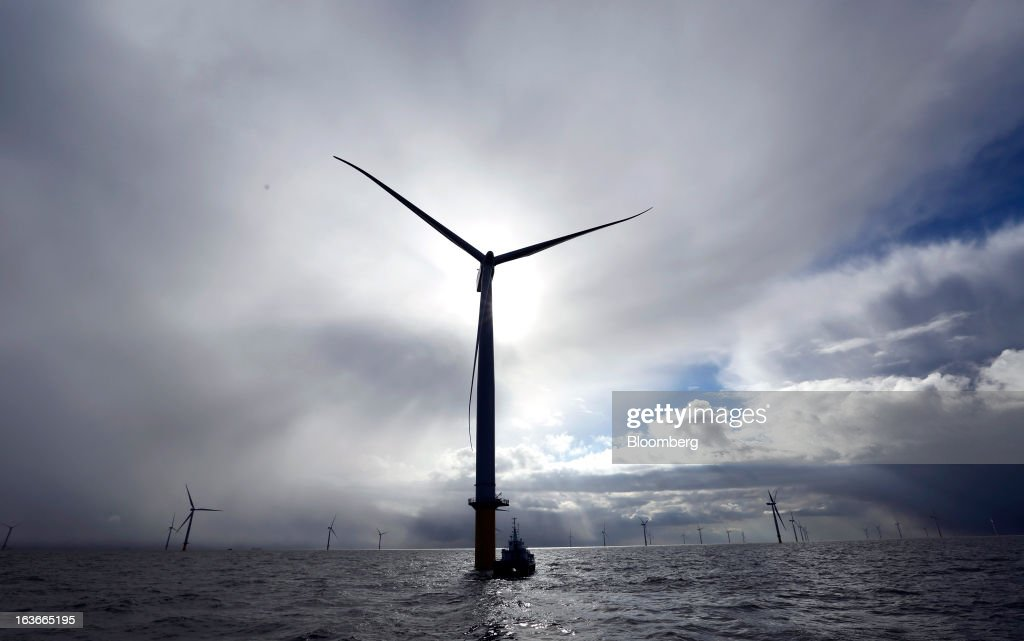 A service boat sits moored alongside a wind turbine at the London Array project, the world's largest consented wind farm, a partnership between Dong Energy A/S, E.ON AG and Abu Dhabi-based Masdar in the Thames Estuary, U.K., on Wednesday, March 13, 2013. 'London Array will soon be the largest operational offshore wind farm in the world,' said Benj Sykes, head of Dong Energy's U.K. wind business. Photographer: Chris Ratcliffe/Bloomberg via Getty Images
