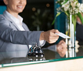 Caucasian female is giving key for hotel room to guest at reception desk.