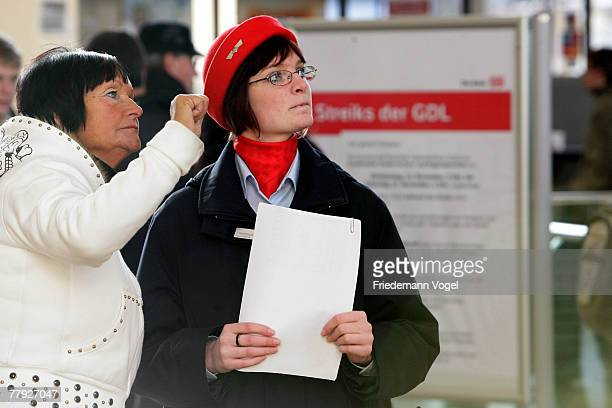 Service employees of Deutsche Bahn AG inform passengers at the main train station during the German locomotive drivers union strike at the Hanover...