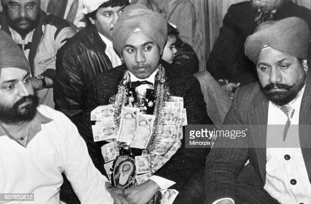 A service for 18 year old Jaspal Singh celebrating his engagement with gifts of money from other worshippers which form a garland around his neck at...