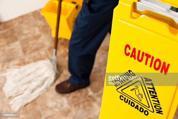 Service Industry:  Caution sign and janitor mopping retail store floor