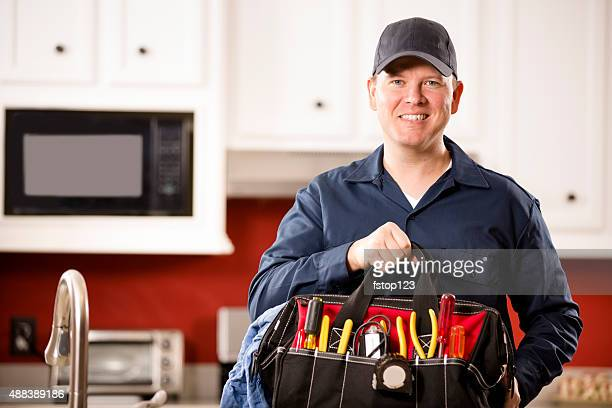 Service Industry:  Mid-adult repairman working at customer's home. Tools.