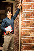 Latin descent repairman or inspector points toward home exterior. Clipboard.