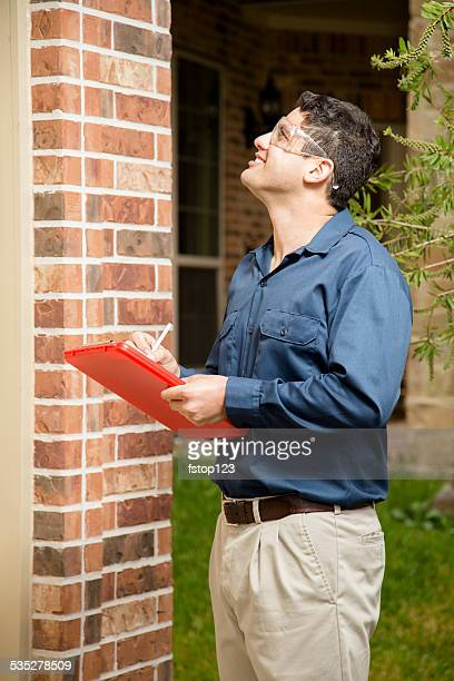 Service Industry: Repairman or inspector outside a residential home. Clipboard.