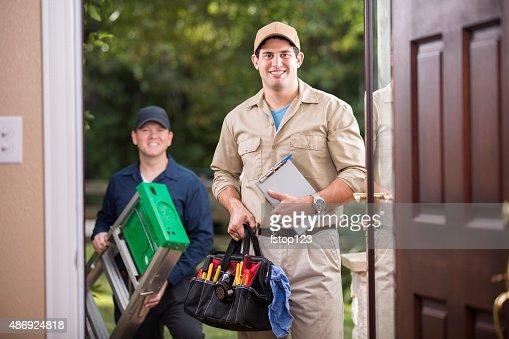 Service Industry: Two multi-ethnic repairmen at customer's front door.