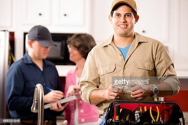 Service Branche: Zwei multi-ethnischen repairmen Arbeit an Kunden zu Hause fühlen.