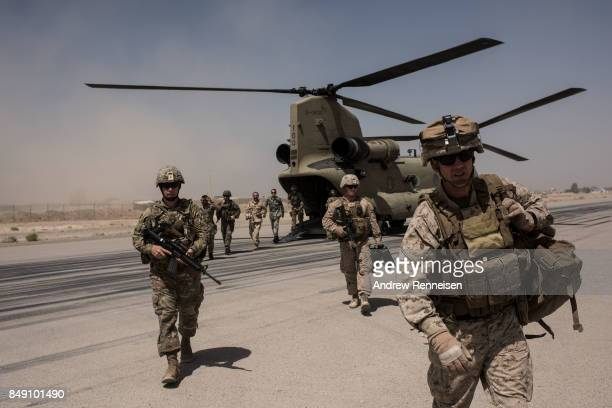 S service members walk off a helicopter on the runway at Camp Bost on September 11 2017 in Helmand Province Afghanistan About 300 marines are...