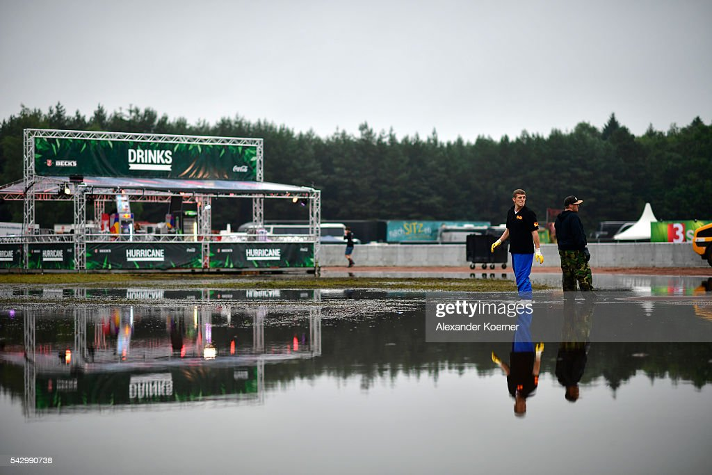 Service personal stand in a puddle at the Hurricane Festival compound on June 25, 2016 in Scheessel, Germany. The Hurricane Festival was evacuated yesterday and was delayed today for the late evening, following heavy rain and thunderstorm alerts. The rain and thunderstorm have hit the festival during the night and day, causing damage to tents and flooded the festival site, only 7 concerts can be played on two stages today. The Hurricane Festival celebrates this year its 25th anniversary. 75.000 music fans have visited the Festival, but some thousands have already left the compound due to the current situation.