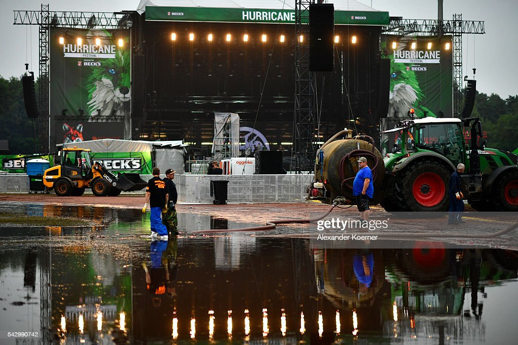 Service personal stand in a puddle in front of the Green Stage at the Hurricane Festival compound on June 25, 2016 in Scheessel, Germany. The Hurricane Festival was evacuated yesterday and was delayed today for the late evening, following heavy rain and thunderstorm alerts. The rain and thunderstorm have hit the festival during the night and day, causing damage to tents and flooded the festival site, only 7 concerts can be played on two stages today. The Hurricane Festival celebrates this year its 25th anniversary. 75.000 music fans have visited the Festival, but some thousands have already left the compound due to the current situation.